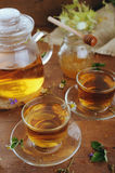 Teapot and cups of herbal tea and jar of honey on wooden table Stock Photo