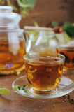 Teapot and cups of herbal tea on wooden table Stock Images