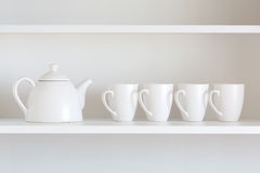 Teapot and cups on the shelf Royalty Free Stock Image