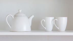 Teapot and cups on the shelf Royalty Free Stock Photo