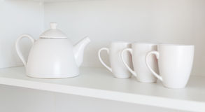 Teapot and cups on the shelf Stock Images