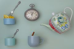 Teapot with cups, and spoons and watch stock images