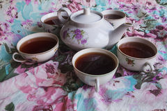 Teapot and cups with tea. Tea and five cups of black tea on a background of fabric with floral pattern Royalty Free Stock Images