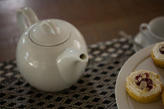 Teapot and dessert on place mat Royalty Free Stock Photo