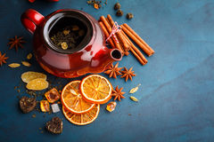 Teapot with dry tea. Dried oranges, cinnamon sticks and anise on a blue background. Free space for text Royalty Free Stock Photos