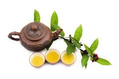Teapot e copos da argila com folhas de chá fotografia de stock royalty free