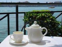 Teapot e um copo na tabela Fotografia de Stock Royalty Free