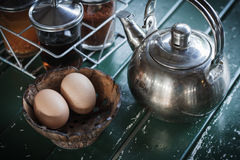 Teapot and egg in wooden cup. In breakfast time Stock Photography