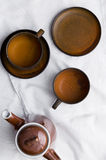 Teapot and empty brown tea cups Stock Photos