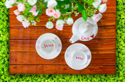 Teapot, empty teacup and artificial flowers on. Top view of the teapot, empty teacup or coffee cup and artificial flowers on a wooden and green clover, Love of stock images