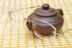 Teapot and Eye Glasses. Small brown earthenware teapot with eyeglasses balancing on the spout royalty free stock image