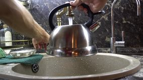 The teapot in a sink. The teapot is filled with tap water from under the crane stock video