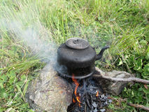 Teapot on the fire outdoors Stock Photography