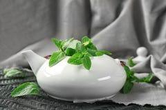 Teapot with fresh lemon balm leaves. On table Stock Photo