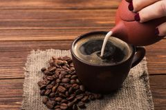 Milk pour into a coffee cup Royalty Free Stock Images