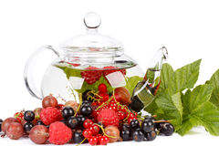 Teapot with fruit tea and green leaves Stock Images