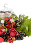 Teapot with fruit tea and green leaves Royalty Free Stock Photo