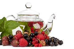 Teapot with fruit tea and green leaves Royalty Free Stock Image