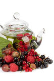 Teapot with fruit tea and green leaves Stock Image