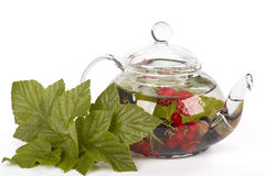 Teapot with fruit tea and green leaves Royalty Free Stock Photos