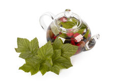Teapot with fruit tea and green leaves Royalty Free Stock Photography