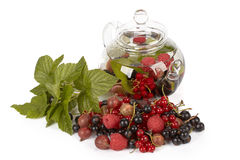 Teapot with fruit tea and green leaves Stock Photo