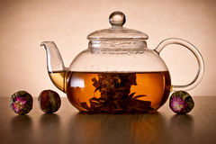 Teapot and glass cup with blooming tea flower. Stock Images
