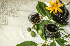 Teapot with a glass jar  jam of nuts on leaves with orange lilies on an embroidered tablecloth Stock Photography