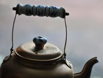 Teapot - Golden Brass Bronze Tea Pot - With Blue and White Ename. L Handle with muted gray Abstract Mood Background royalty free stock image