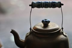 Teapot - Golden Brass Bronze Tea Pot - With Blue and White Ename. L Handle with muted gray Abstract Mood Background royalty free stock images