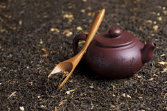 Teapot with green tea. Teapot staing on the green tea with wood spoon Stock Photography