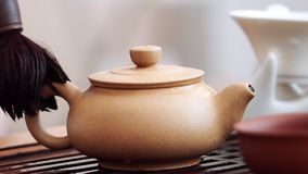 Teapot with green tea, wipe with a brush of tea drops.  stock video footage