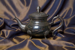 Teapot on a grey drapery background. A silver retro teapot on a grey and violet drapery background Royalty Free Stock Images