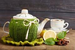 Teapot with handmade knitted cover, lemon, cinnamon, mint Stock Photo