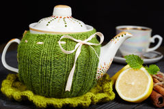 Teapot with handmade knitted cover, lemon, cinnamon, mint Royalty Free Stock Photos
