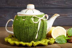 Teapot with handmade knitted cover, lemon, cinnamon, mint Royalty Free Stock Image