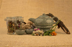 Teapot with herbs and roots. Ready fot tea over textured background Stock Images