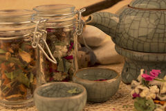 Teapot with herbs and roots. Ready fot tea over textured background Stock Photos