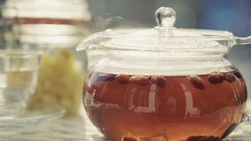 Teapot with hot tea at outdoor. Is a stock video that exhibits excellent footage of the table with hot drinks in frosty weather. This 3840x2160 4K video is stock video footage