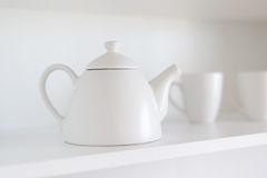 Teapot i filiżanki na półce Fotografia Stock