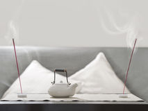 Teapot and incense stick on table Stock Photo