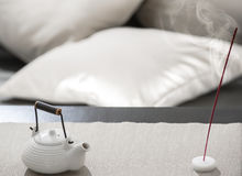 Teapot and incense stick on table Royalty Free Stock Photos