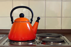 Teapot on Kitchen Oven. Cooking tea in an orange Kettle on an electronic stove Stock Photo