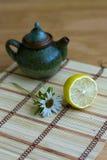Teapot and lemon. On canvas stock photo