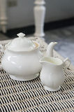 Teapot with little milk jar Stock Photography