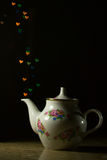 TeaPot of love. White Ceramic TeaPot with print and heart bokeh background Royalty Free Stock Images