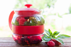 Teapot with mint and red raspberries Stock Images