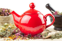 Teapot, mortar and pestle with healing herbs Stock Photos