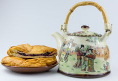 Teapot and muffin on a plate. East Asian teapot with drawings and muffin on a plate Royalty Free Stock Photo