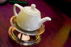 Teapot no trivet na luz morna fotografia de stock